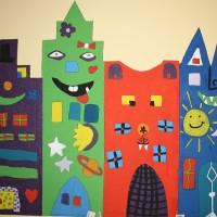 Die Wände auf dem Schulflur der Klassen 3/4 wurden an den Projekttagen von den Kindern mit vielen bunten Häusern nach James Rizzi gestaltet.